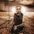 Woman with a spear in a desert — Stock Photo