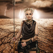 Stock Photo: Woman with a spear in a desert