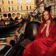 Beautiful woman in red cloak riding on gondola — Stock Photo