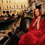 Beautiful woman in red cloak riding on gondola — Stock Photo
