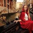 Beautiful woman in red cloak riding on gandola — Stock Photo