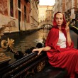 Stock Photo: Beautiful womin red cloak riding on gandola