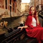 Beautiful woman in red cloak riding on gandola — Stock Photo