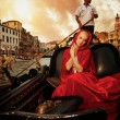 Beautiful womin red cloak riding on gondola — Stock Photo #12742213