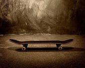 Skateboard against grunge wall — Stock Photo