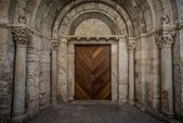 Wooden door in ancient archway — Stock Photo