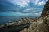 Gloomy sky over rocky shore — Stock Photo