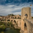Ancient romanesque bridge over river, Besalu - Stock Photo