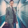 Man in classic grey suit with briefcase standing on escalator — Stock Photo