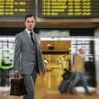 Man in classic grey suit with briefcase in airport - Stock Photo