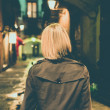 Blond woman in raincoat walking alone outdoors at night — Stok fotoğraf