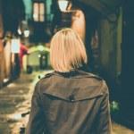 mulher loira na capa de chuva andando sozinho ao ar livre à noite — Foto Stock