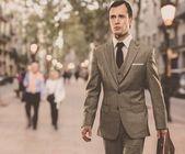 Mann im klassischen grauen anzug mit aktentasche walking im freien — Stockfoto