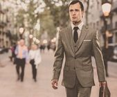 Man in classic grey suit with briefcase walking outdoors — Stock Photo