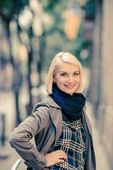 Beautiful smiling blond woman wearing blue scarf outdoors — Stock Photo
