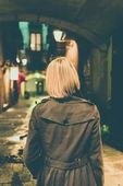 Blond woman in raincoat walking alone outdoors at night — Stock Photo