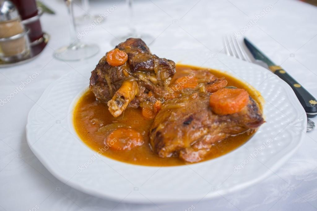 Two pieces of lamb in sauce on plate — Stock Photo #14220831