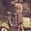 Woman in retro dress with a scooter — Stock Photo #14551023