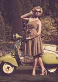 Woman in retro dress with a scooter — Stockfoto