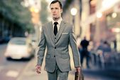 Man in classic grey suit with briefcase walking outdoors — Zdjęcie stockowe
