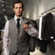 Businessman in classic vest against row of suits in shop — Stock Photo #14859913