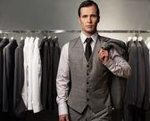 Affärsman i klassiska västen mot raden av passar i butik — Stockfoto
