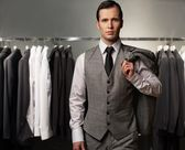 Businessman in classic vest against row of suits in shop — Zdjęcie stockowe