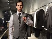 Businessman in classic vest against row of suits in shop — Fotografia Stock