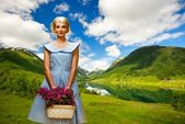 Lovely woman in blue dress with flowers against lake view — Stock Photo