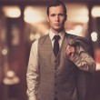 Man in waistcoat with jacket over his shoulder against blurred background — Stock Photo