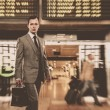 Man in classic grey suit with briefcase in airport — Stock Photo #15657219