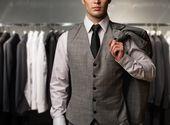 Biznesmen w klasyczny vest przeciwko wiersz odpowiada w sklepie — Zdjęcie stockowe