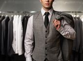Businessman in classic vest against row of suits in shop — Stok fotoğraf
