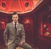 Hombre confiado en clásico traje gris, sentado en la silla en el gabinete — Foto de Stock