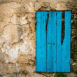 Window closed with damaged shutters in old wall — Stock Photo
