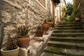Flower pots on narrow medieval street — Stock Photo