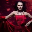 Beautiful vampire woman in red dress - Stock Photo
