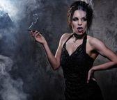 Beautiful vampire woman in black dress smoking — Stock Photo