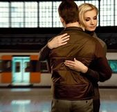 Beautiful couple embracing on train station — Stock Photo
