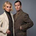 Elegant couple in coats isolated on grey — Stock Photo