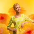 Young woman among big yellow flowers - Stock fotografie