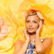 Young woman among big yellow flowers - Foto Stock