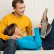 Happy young man and woman with newspaper on sofa in home interior - Stock Photo
