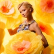 Woman among big yellow flowers — Stock Photo