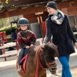 Mother riding her son on a pony wearing protective helmet — Stock Photo