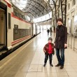 Royalty-Free Stock Photo: Happy mother with her son on train station platform