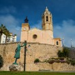 Statue of a woman against church of Sant Bartomeu i Santa Tecla in Sitges - Stock Photo