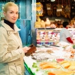 Young blond woman buying fish on market — Stock Photo