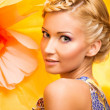 Beautiful young cheerful blond woman in colourful dress among big yellow flowers - Stock Photo