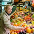 Young cheerful blond woman choosing fresh fruits on market - Stock Photo